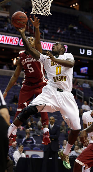 Photo - George Mason guard Bryon Allen (0) shoots in front of Oklahoma guard Je'lon Hornbeak (5) during the first half of an NCAA college basketball game in the BB&T Classic, Sunday, Dec. 8, 2013, in Washington. Oklahoma won 81-66. (AP Photo/Alex Brandon)