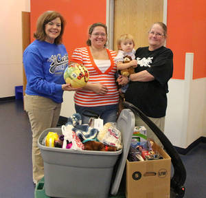 Photo - Chrissy Hancock, left, chairman of the J.D. McCarty Center outpatient Christmas committee, presents donations to Rebecca Burns, center, and her mother, Penny Bailey, who is holding Burns' daughter Faith. PHOTO PROVIDED <strong></strong>