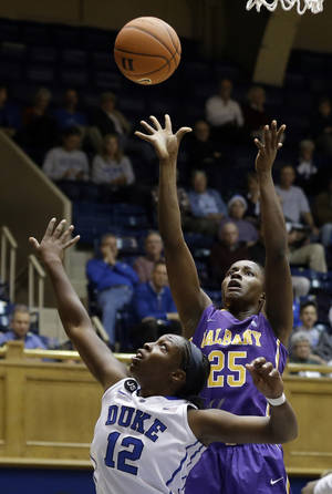 Photo - Duke's Chelsea Gray (12) defends as Albany's Shereesha Richards (25) shoots during the second half of an NCAA college basketball game in Durham, N.C., Thursday, Dec. 19, 2013. Duke won 80-51. (AP Photo/Gerry Broome)