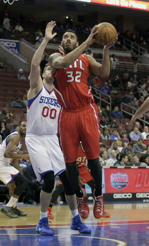 Photo - Atlanta Hawks' Mike Scott (32) shoots as Philadelphia 76ers' Spencer Hawes (00) defends in the second half of an NBA basketball game, Friday, Jan. 31, 2014, in Philadelphia. The Hawks won 125-99. (AP Photo/H. Rumph Jr.)