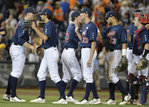 Photo - Vanderbilt coach Tim Corbin, left, celebrates with his players after Vanderbilt defeated Virginia 9-8 in the opening game of the best-of-three NCAA baseball College World Series finals in Omaha, Neb., Monday, June 23, 2014. (AP Photo/Ted Kirk)