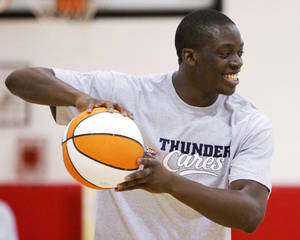 Photo - NBA BASKETBALL / CHILD / KIDS: Oklahoma City Thunder draft pick Reggie Jackson holds the ball as he works with children during a Thunder Youth Basketball Camp at the Boys and Girls Club of Oklahoma County  in Oklahoma City, Saturday, June 25, 2011. The Thunder selected Reggie Jackson with the 24th pick in this year's NBA draft. Photo by Nate Billings, The Oklahoman ORG XMIT: KOD
