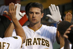 Photo - Pittsburgh Pirates' Jordy Mercer (10) celebrates with teammates in the dugout after hitting a solo home run off Milwaukee Brewers starting pitcher Kyle Lohse during the fifth inning of a baseball game in Pittsburgh Friday, June 6, 2014. (AP Photo/Gene J. Puskar)