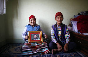 Photo - Nimdige Sherpa holds a portrait of her son Ang Kaji Sherpa, killed in an avalanche on Mount Everest, with her husband Ankchu Sherpa seated beside her in their rented apartment in Katmandu, Nepal, Wednesday, April 23, 2014. Dozens of Sherpa guides packed up their tents and left Mount Everest's base camp Wednesday, after the avalanche deaths of 16 of their colleagues exposed an undercurrent of resentment by Sherpas over their pay, treatment and benefits. (AP Photo/Niranjan Shrestha)