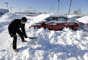 Photo - A salesmen at a car dealership digs out cars covered in snow Jan. 7 at a dealership in Indianapolis .   AP File Photo <strong>Michael Conroy - AP</strong>