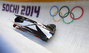 Photo - The two-man team from the United States USA-1, piloted by Steven Holcomb, speeds down the track during the men's two-man bobsled training at the 2014 Winter Olympics, Thursday, Feb. 13, 2014, in Krasnaya Polyana, Russia. (AP Photo/Natacha Pisarenko)