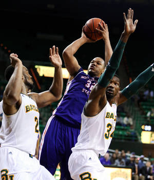 Photo - Northwestern State forward DeQuan Hicks (32), center, shoots over forward Cory Jefferson (34), right, and  Rico Gathers (2), left, in the first half of an NCAA college basketball game, Wednesday, Dec. 18, 2013, in Waco, Texas. (AP Photo/Waco Tribune Herald, Rod Aydelotte)