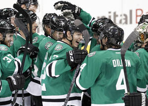Photo - Dallas Stars' Alex Chiasson, center, celebrates with teammates on the ice following after their NHL hockey game against the San Jose Sharks, Thursday, Oct. 17, 2013, in Dallas. Chiasson scored a shootout goal that helped the Stars to the 4-3 win. (AP Photo/Tony Gutierrez)