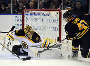 Photo - Boston Bruins' goaltender Anton Khudobin (35), of Kazakhstan, makes a save on Buffalo Sabres' left winger Nathan Gerbe (42) during the first period of an NHL hockey game in Buffalo, N.Y., Sunday, Feb. 10, 2013. (AP Photo/Gary Wiepert)