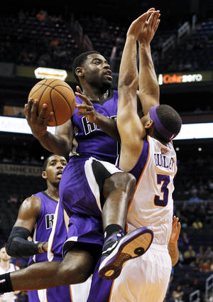photo -   Sacramento Kings' Tyreke Evans tries to drive around Phoenix Suns' Jared Dudley (3) as Kings' Jason Thompson, back left, looks on during the first half of an NBA preseason basketball game, Monday, Oct. 22, 2012, in Phoenix. (AP Photo/Ross D. Franklin)