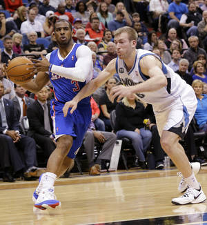 Photo - Los Angeles Clippers guard Chris Paul (3) drives against Minnesota Timberwolves forward Robbie Hummel (6) during the second quarter of an NBA basketball game in Minneapolis, Monday, March 31, 2014.  (AP Photo/Ann Heisenfelt)