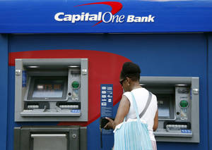 Photo - FILE - In this July 18, 2013, file photo, a woman uses a Capital One Bank automated teller machine in New York. Capitol One reports quarterly earnings on  Thursday, Oct. 17, 2013.  (AP Photo/Mark Lennihan, File)