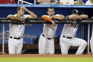 Photo - Miami Marlins right fielder Giancarlo Stanton, center, watches with his teammates from the dugout in the ninth inning during a baseball game against the Los Angeles Dodgers, Thursday, Aug. 22, 2013 in Miami. The Dodgers defeated the Marlins 6-0. (AP Photo/Lynne Sladky)