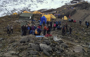 photo -   In this photo provided by Nepalese airline Simrik Air, rescuers attend to injured victims, unseen, after an avalanche at the base camp of Mount Manaslu in northern Nepal, Sunday, Sept. 23, 2012. The avalanche swept away climbers on a Himalayan peak in Nepal on Sunday, leaving at least nine dead and six others missing, officials said. (AP Photo/Simrik Air)
