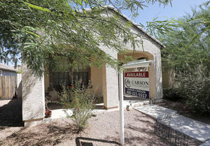 Photo - FILE - In  this Tuesday, July 30, 2013, file photo, a realty sign hangs in front of a home for sale in Gilbert, Ariz. Standard & Poor's/Case-Shiller reports on home prices in July on Tuesday, Sept. 24, 2013.  (AP Photo/Matt York, File)