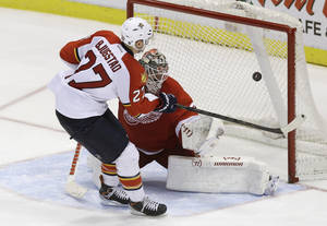 Photo - Florida Panthers center Nick Bjugstad (27) shoots the puck past Detroit Red Wings goalie Jonas Gustavsson (50) of Sweden for a goal during the shootout period of an NHL hockey game in Detroit, Sunday, Jan. 26, 2014. (AP Photo/Carlos Osorio)