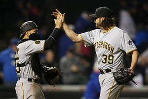 Photo - Pittsburgh Pirates catcher Russell Martin (55) and relief pitcher Jason Grilli (39) celebrate after defeating the Chicago Cubs in the MLB National League baseball game on Tuesday, April 8, 2014, in Chicago. The Pittsburgh Pirates won 7-6. (AP Photo/Andrew A. Nelles)