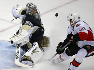 Photo - Pittsburgh Penguins goalie Marc-Andre Fleury (29) makes a save on a shot by Ottawa Senators' Mika Zibanejad (93) in the first period of an NHL hockey game in Pittsburgh, Monday, Feb. 3, 2014. (AP Photo/Gene J. Puskar)