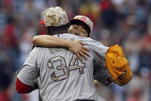 Photo - Boston Red Sox pitcher, Koji Uehara (19) hugs David Ortiz (34) after they defeated the Atlanta Braves 8-6 in the ninth inning of a baseball game on Monday, May 26, 2014, in Atlanta, Ga. (AP Photo/Butch Dill)