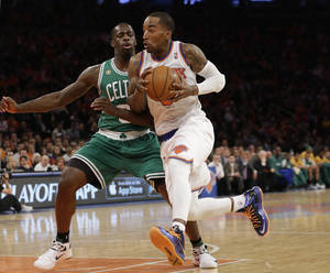 Photo - New York Knicks guard J.R. Smith, right, drives past Boston Celtics forward Jeff Green (8) during the first half of Game 1 in the first round of the NBA basketball playoffs at Madison Square Garden in New York, Saturday, April 20, 2013.  (AP Photo/Kathy Willens)