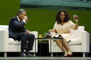 Photo - Howard Schultz, left, chairman and CEO of Starbucks Coffee Company, sits and drinks tea with Oprah Winfrey, right, to announce their partnership to offer Teavana Oprah Chai tea, Wednesday, March 19, 2014, at Starbucks' annual shareholders meeting in Seattle. (AP Photo/Ted S. Warren)