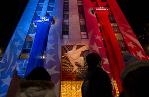 photo -   People watch early election results displayed on a utility lift suspended from the front of the GE Building at Rockefeller Center New York, Tuesday, Nov. 6, 2012. (AP Photo/Craig Ruttle)