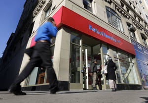 Photo - People pass a Bank of America brach, in New York,  Monday, Jan. 7, 2013. Bank of America will pay $10.3 billion to the government mortgage agency Fannie Mae to settle claims resulting from mortgage-backed investments that soured during the housing crash.  (AP Photo/Richard Drew)