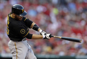 Photo - Pittsburgh Pirates' Russell Martin follows through on an RBI single during the first inning of a baseball game against the St. Louis Cardinals Thursday, July 10, 2014, in St. Louis. (AP Photo/Jeff Roberson)