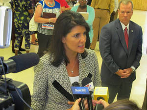 Photo - South Carolina Gov. Nikki Haley listens to a question while meeting with reporters in Atlantic Beach, S.C., on Tuesday, July 29, 2014. The governor had just urged town council to work with her to end the Atlantic Beach Bikefest following violence in the Myrtle Beach area last Memorial Day. She said the state is willing to work to help redevelop the community to make it a family-friendly tourist destination. To Haley's left is Duane Parrish, the director of the South Carolina Department of Parks, Recreation and Tourism.  (AP Photo/Bruce Smith)