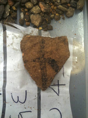 Photo -   In this May 2012 photo provided by Bryce Barker, a fragment of Aboriginal rock art on granite found in Australian Outback is seen on a plastic bag. University of Southern Queensland archaeologist Bryce Barker said Monday, June 18, 2012 that tests show the Aboriginal rock art in the cave was made 28,000 years ago, making it the oldest in Australia and among the oldest in the world. The rock art was made with charcoal, so radiocarbon dating could be used to determine its age. (AP Photo/Bryce Barker) EDITORIAL USE ONLY