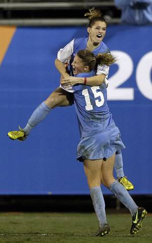Photo - North Carolina's Kealia Ohai, above, celebrates her goal in overtime with teammate Katie Bowen (15) after beating Stanford in an NCAA women's college soccer semifinal game Friday, Nov. 30, 2012, in San Diego. North Carolina won, 1-0. (AP Photo/Gregory Bull)