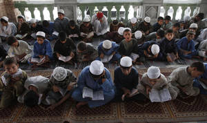 Photo -   Afghan boys read the Quran during the Muslim holy month of Ramadan at a mosque in the city of Jalalabad, the provincial capital of Nangarhar province, east of Kabul, Afghanistan, Sunday, July 22, 2011. Muslims from Morocco to Afghanistan are experiencing the toughest Ramadan in more than three decades with no food or drink, not even a sip of water, for 14 hours a day during the hottest time of the year. (AP Photo/ Rahmat Gul)