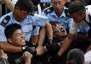 Photo - Protesters are taken away by police officers after hundreds of protesters staged a peaceful sit-ins overnight on a street in the financial district in Hong Kong Wednesday, July 2, 2014, following a huge rally to show their support for democratic reform and oppose Beijing's desire to have the final say on candidates for the chief executive's job. (AP Photo/Kin Cheung)