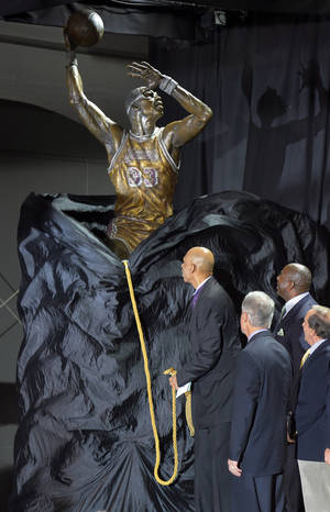 "Photo -   Former Los Angeles Lakers center Kareem Abdul-Jabbar, left, unveils a statue of himself in front of Staples Center as Earvin ""Magic"" Johnson, second from right, looks on, Friday, Nov. 16, 2012, in Los Angeles. (AP Photo/Mark J. Terrill)"