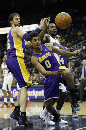 Photo - Atlanta Hawks' Paul Milsap, center right, chases the loose ball with Los Angeles Lakers' Nick Young (0) and Pau Gasol (16)  in the first half of an NBA basketball game, Monday, Dec. 16, 2013, in Atlanta. (AP Photo/John Bazemore)