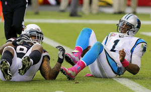 Photo - Carolina Panthers' Cam Newton (1) gets up slowly after being hit by Arizona Cardinals' Darnell Dockett in the second half of an NFL football game on Sunday, Oct. 6, 2013, in Glendale, Ariz.  The Cardinals defeated the Panthers 22-6. (AP Photo/Ross D. Franklin)