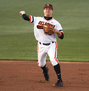 Photo - Oklahoma State's Donnie Walton (5) throws the ballk to first base during an NCAA college baseball game between Oklahoma State University (OSU) and Texas Christian University (TCU) at Allie P. Reynolds stadium in Stillwater, Okla., Friday, March 28, 2014. The series is the Cowboys' Big 12 home opener in the 2014 season. Photo by KT King, The Oklahoman