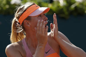 Photo - Russia's Maria Sharapova realizes she won the final of the French Open tennis tournament against Romania's Simona Halep at the Roland Garros stadium, in Paris, France, Saturday, June 7, 2014. Sharapova won in three sets 6-4, 6-7, 6-4. (AP Photo/Darko Vojinovic)