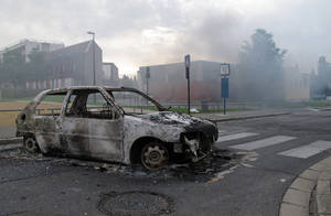 photo -   The shell of a burnt out car is seen in a neighborhood of Amiens, France, Tuesday, Aug. 14, 2012. Dozens of young men rioted in a troubled district in northern France after weeks of tensions, pulling drivers from their cars and stealing the vehicles, and burning a school and a youth center. The police department in Amiens says at least 16 officers were hurt by the time the riot ended Tuesday, some by buckshot. (AP Photo/Georges Charrieres)