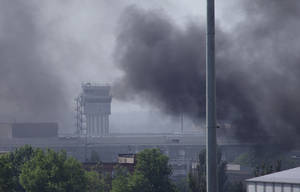 Photo - Smoke rises from the airport outside Donetsk, Ukraine, Monday, May 26, 2014. Ukraine's military launched airstrikes Monday against the separatists who had taken over the airport in the eastern city of Donetsk, suggesting that fighting in the east is far from over. (AP Photo/Ivan Sekretarev)