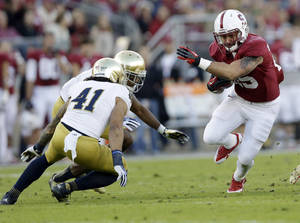 Photo - Stanford running back Tyler Gaffney, right, runs against Notre Dame during the first half of an NCAA college football game on Saturday, Nov. 30, 2013, in Stanford, Calif. Stanford won 27-20. (AP Photo/Marcio Jose Sanchez)