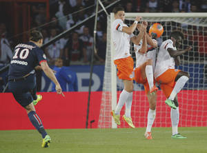 Photo - Paris Saint Germain's Zlatan Ibrahimovic, left, takes a free kick over the wall during his French League one soccer match against Montpellier , Saturday, May. 17, 2014, at the  Parc des Princes stadium, in Paris, France. (AP Photo/Jacques Brinon)