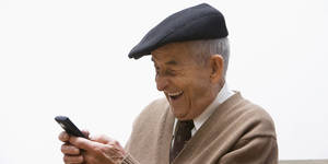 Photo - Senior, Hispanic man text messaging on cell phone