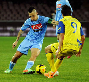 Photo - Napoli's Marek Hamsik, left, faces Chievo Verona's Simone Bentivoglio, during a Serie A soccer match, at the San Paolo stadium in Naples, Italy, Saturday, Jan. 25, 2014. (AP Photo/Salvatore Laporta)