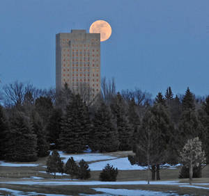 Photo - In this photo taken Wednesday, March 26, 2013, Bismarck, N.D., the full Lenten moon rises from behind the North Dakota capitol in Bismarck, N.D. Early settlers called the last full moon of winter the Lenten moon due to its arrival just before Easter. (AP Photo/The Bismarck Tribune, Tom Stromme)