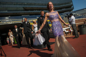 Photo - Durand High School students smile as they enter onto the field at Michigan Stadium on the University of Michigan campus, Saturday, May 10, 2014, in Ann Arbor, Mich. The junior-senior prom for students at Durand High School was the first prom hosted by the 100,000-plus-seat football venue. The group took photos on the field, visited the locker rooms and had their dancing and dinner in the Jack Roth Stadium Club until midnight. (AP Photo/The Flint Journal, Jake May) LOCAL TV OUT; LOCAL INTERNET OUT