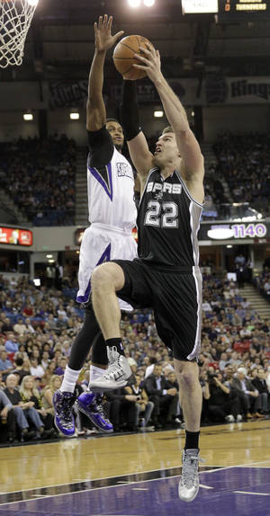 Photo - San Antonio Spurs center Tiago Splitter, right, of Brazil, drives to the basket against Sacramento Kings forward Rudy Gay during the first quarter of an NBA basketball game in Sacramento, Calif., Friday, March 21, 2014.(AP Photo/Rich Pedroncelli)