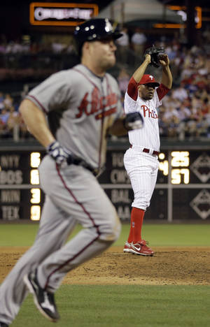Photo -   Philadelphia Phillies' Antonio Bastardo, right, stretches after walking home Atlanta Braves' Matt Diaz in the eighth inning of a baseball game, Friday, July 6, 2012, in Philadelphia. Atlanta won 5-0. (AP Photo/Matt Slocum)