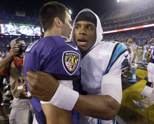 Photo - Carolina Panthers quarterback Cam Newton greets Baltimore Ravens quarterback Joe Flacco, left, at midfield after a preseason NFL football game in Baltimore, Thursday, Aug. 22, 2013. The Panthers defeated the Ravens 34-27. (AP Photo/Patrick Semansky)