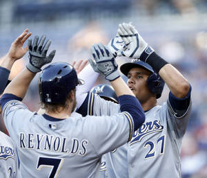 Photo - Milwaukee Brewers first baseman Mark Reynolds (7) is greeted at home plate by teammate  Carlos Gomez (27) after hitting a grand-slam home run in the first inning of a baseball game against Atlanta Braves Wednesday, May 21, 2014,2 in Atlanta.(AP Photo/John Bazemore)